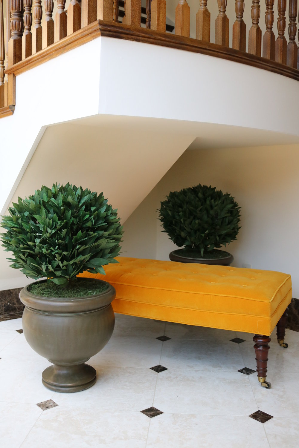 We wanted to soften the space underneath the stairwell, and so added this vintage bench, upholstered in a striking mango velvet from  Designers Guild.  The planters add a welcome touch of green.